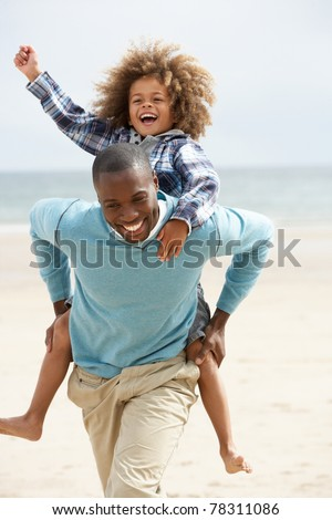 Father and son playing piggyback on beach - stock photo