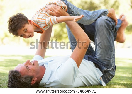 Father And Son Playing Together In Park - stock photo