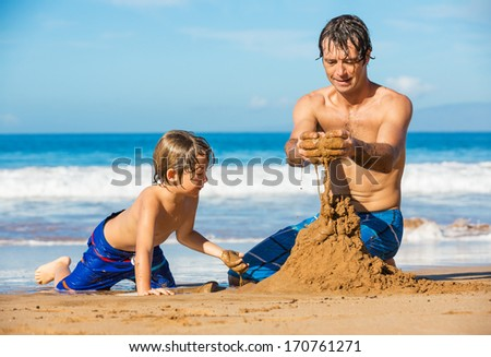 Father and son playing together in the sand on tropical beach, Building sand castle
