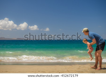Father and son playing together on the beach during summer holidays - stock photo
