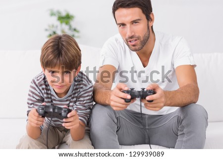 Father and son playing video games on the couch - stock photo