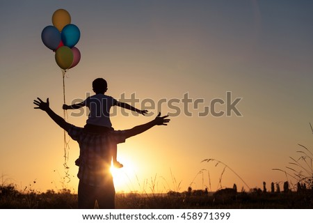 Father and son playing with balloons in the park at the sunset time. People having fun on the field. Concept of friendly family and of summer vacation.