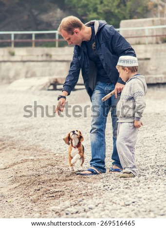 Father and son playing with little puppy on the seaside - stock photo