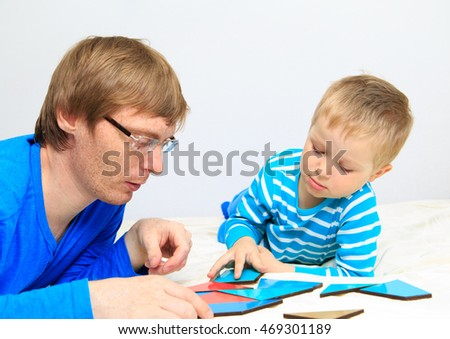 father and son playing with puzzle, early education