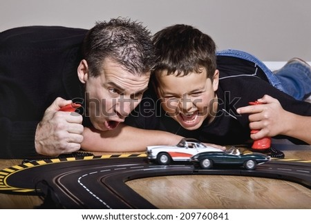 Father And Son Playing With Race Cars - stock photo