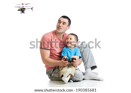 Father and son playing with RC helicopter toy - stock photo