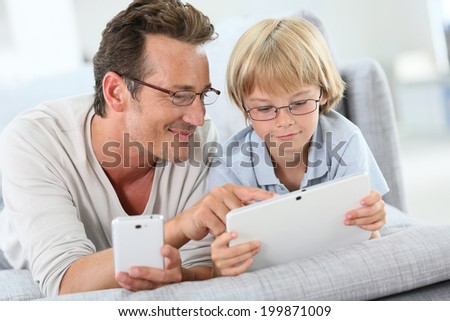 Father and son playing with tablet and smartphone - stock photo