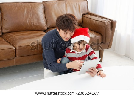Father and son playing with tablet on a  sofa - stock photo