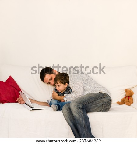 Father and son playing with tablet together on a white sofa - stock photo