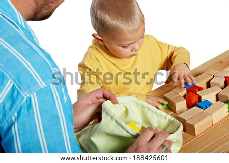 Father and son playing with wooden blocks on studio background - stock photo