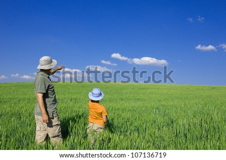 Father and son pointing out at the copy space for your text
