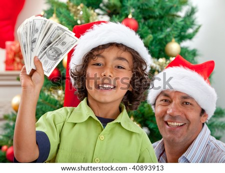 Father and son portrait at Christmas with money - stock photo