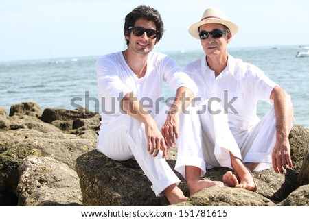 father and son posing at sea resort - stock photo