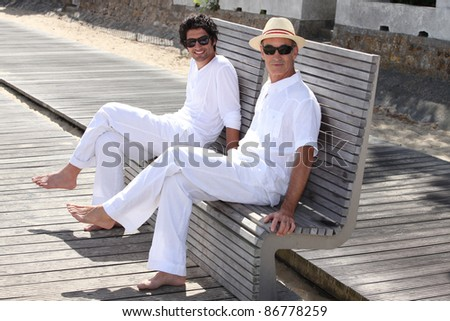 father and son posing together outdoors - stock photo