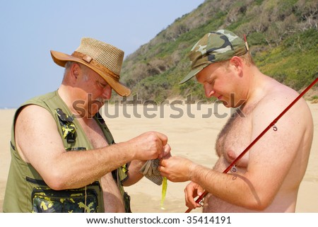 Father and son preparing fishing gear - stock photo