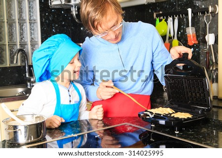 father and son preparing waffles in kitchen interior