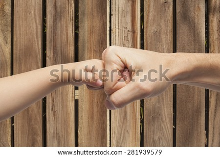 father and son punching fists/hands for agreement over a wooden background - stock photo