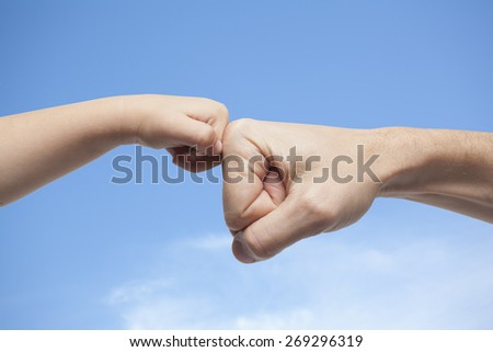 father and son punching for agreement on sky with clouds background - stock photo