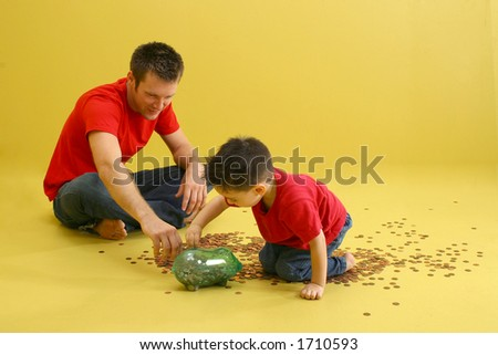 Father and son putting pennies in piggy bank. - stock photo