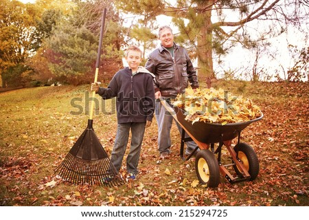 Father and son raking leaves  - stock photo