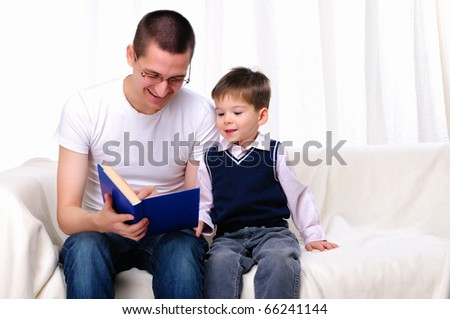 Father and son reading a book together on the couch - stock photo