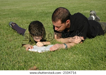Father and son reading book - stock photo