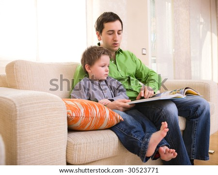 Father and son reading book together at home - stock photo