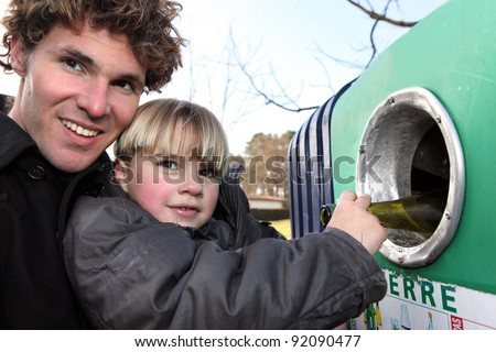 Father and son recycling glass bottles - stock photo