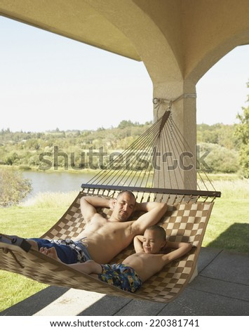 Father and son relaxing in a hammock - stock photo