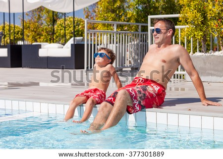 Father and son relaxing near a swimming pool  at the day time. Concept of friendly family.