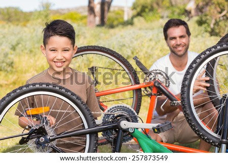 Father and son repairing bike together on a sunny day - stock photo