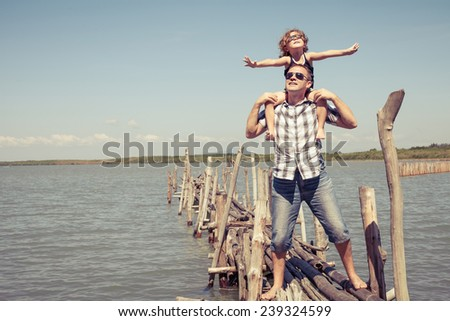 Father and son resting on the bridge in the sea at the day time. Concept of friendly family. - stock photo