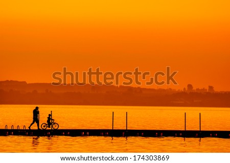 Father and son riding bike silhouettes on the lake at sunset - stock photo