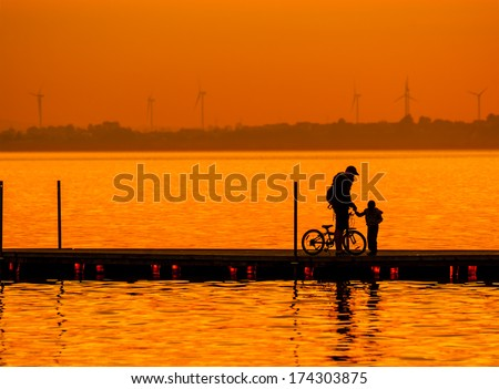 Father and son riding bike silhouettes on the lake at sunset