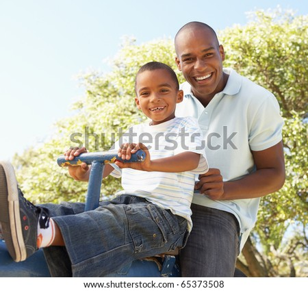Father and Son Riding On SeeSaw In Park - stock photo