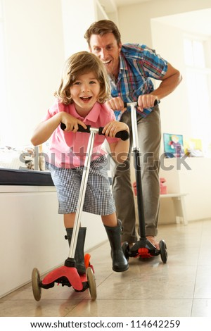 Father And Son Riding Scooters Indoors - stock photo