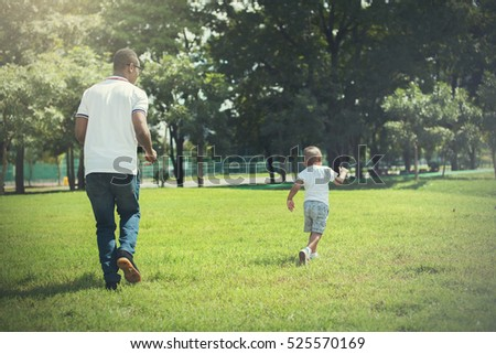 Father and son running and chasing each other in green park