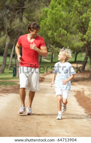 Father and son running in park - stock photo