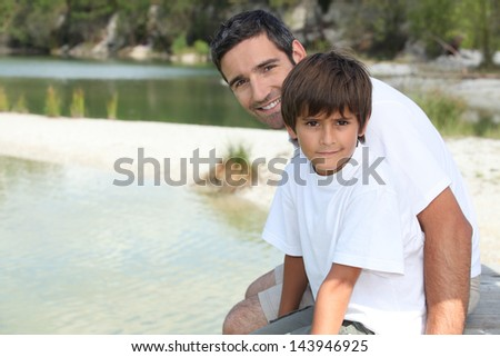 Father and son sat by the lake - stock photo