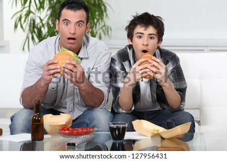 Father and son sat on the sofa eating burgers - stock photo
