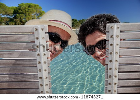 Father and son sat poolside - stock photo