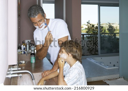 Father and son shaving in the bathroom.