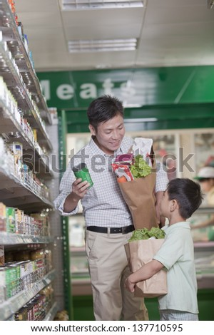 Father and son shopping together in supermarket, Beijing - stock photo