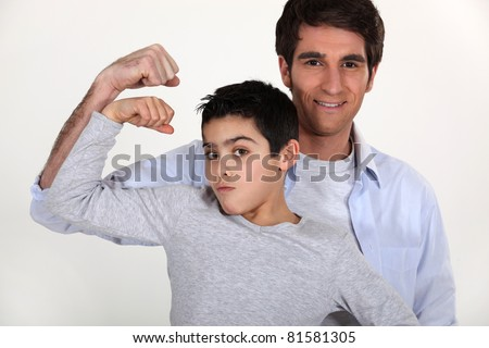 father and son showing muscles - stock photo