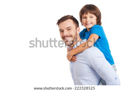 Father and son. Side view of happy father carrying his son on back and smiling while both standing isolated on white