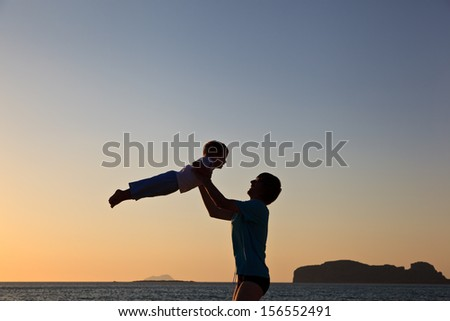 father and son silhouettes at the beach - stock photo