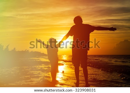 father and son silhouettes play at sunset beach - stock photo