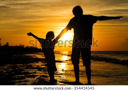 father and son silhouettes play at sunset beach
