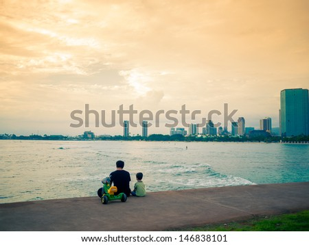 Father and son sit by the sea with cityscape background - stock photo