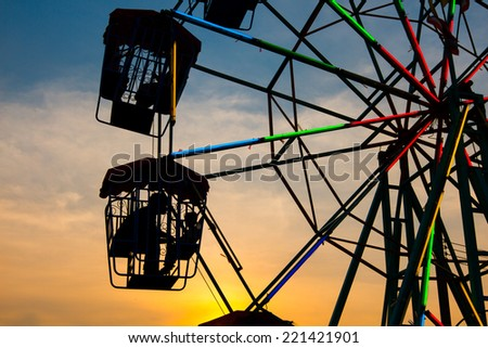 Father and son sit on a ferris at sunset - stock photo